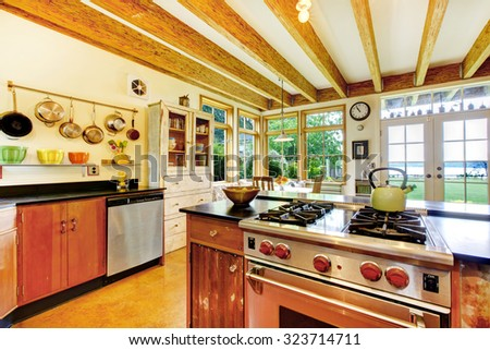 Art modern Vintage style kitchen with creative decor, large wood beams, many windows. - stock photo