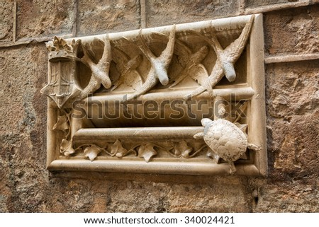 Art nouveau style stone mailbox decorated with swallows and turtle figurines on the wall of Casa de l'Ardiaca, Gothic quarter, Barcelona, Catalonia, Spain