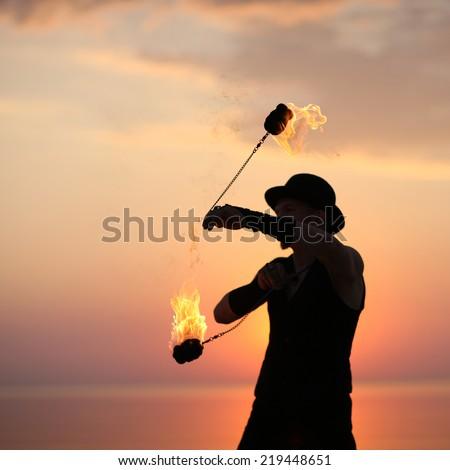 Art of fire dance; spinning fire poi - stock photo