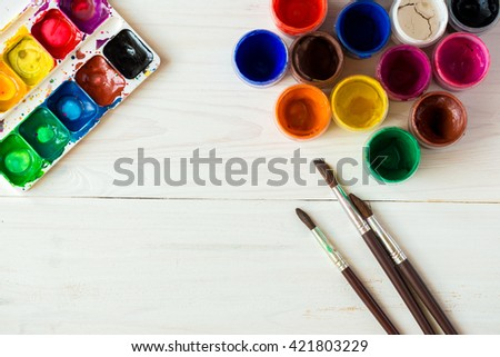 Art of Painting. Painting set: brushes, paints, watercolor, acrylic paint on a white wooden background top down view - stock photo