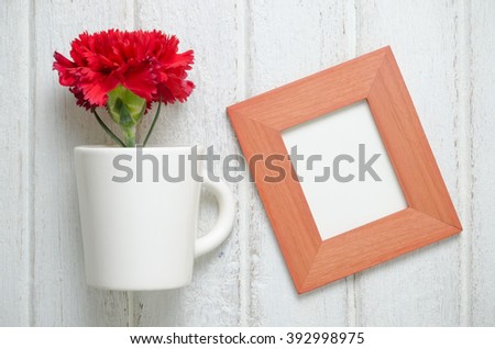 art of red Carnation flower with wooden frame on white wooden  background - stock photo