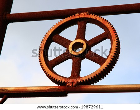 art of rusty and metallic gear wheel of old industry with blue sky - stock photo
