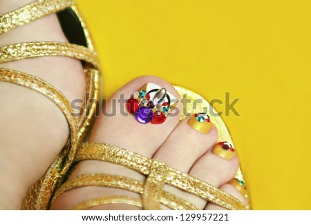 Art pedicure with crystals in sandals for women's nails on a yellow background. - stock photo