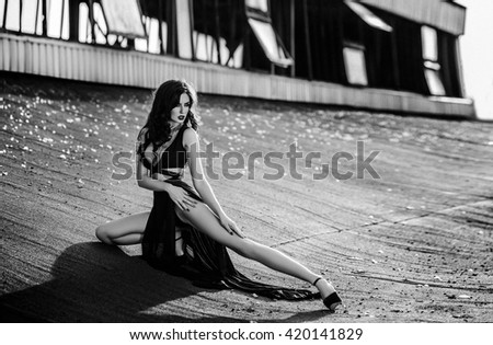 Art photo, black and white, soft focus. Beautiful, sexy brunette girl with long hair, hairdo, make-up, in a revealing black dress posing on the street on a background of the house in the gothic style. - stock photo