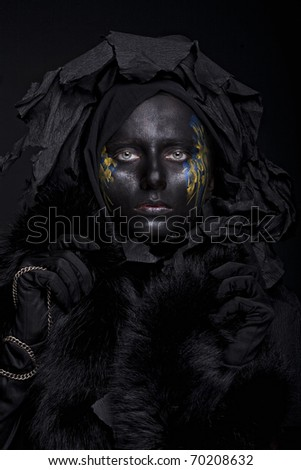 art photo of a beautiful woman with black face over black background - stock photo