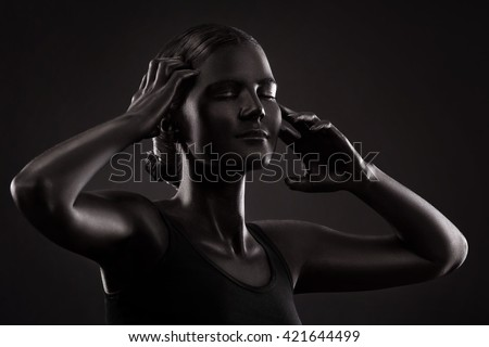 art photo of an artistic woman painted with black color, over black background, portrait in low key - stock photo