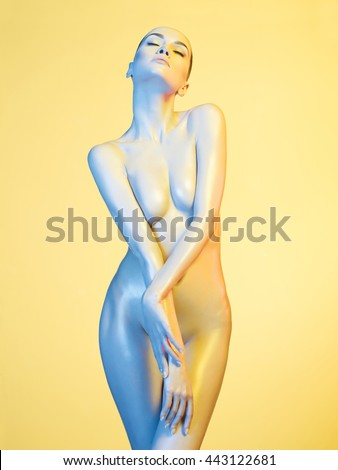 art photo of beautiful nude sexy model in the light colored spotlights - stock photo