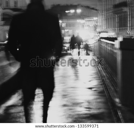 Art photo.Silhouette of a man walking at night on the wet asphalt. - stock photo