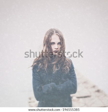 Art portrait of a beautiful brunette in snow and fog