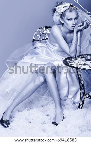 Art portrait of a beautiful female model over snowy background.  Fashion, beauty. - stock photo