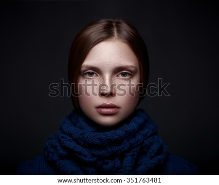 Art portrait of a beautiful young girl with freckles in a sweater and scarf on a dark background.  - stock photo