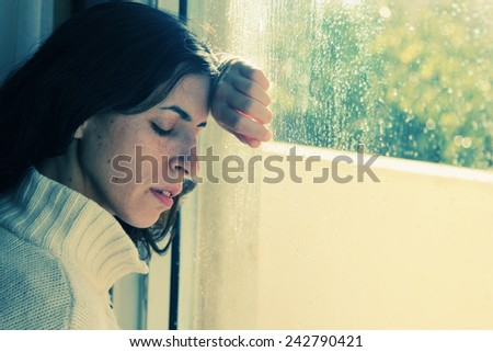 Art portrait of a beautiful young sadly girl looking through the window - stock photo
