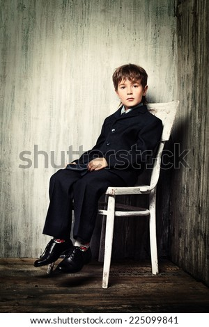 Art portrait of a boy in a suit sitting on a white chair. Educational concept.  - stock photo
