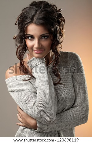 Art portrait of beautiful and attractive woman with curls over a yellow light spot - stock photo