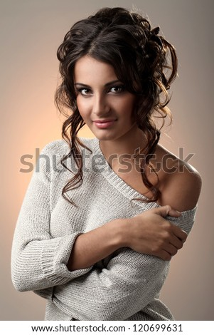 Art portrait of beautiful and attractive woman with curls over a yellow light spot