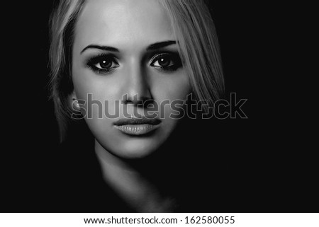 art portrait of beautiful blond woman. black background.monochrome
