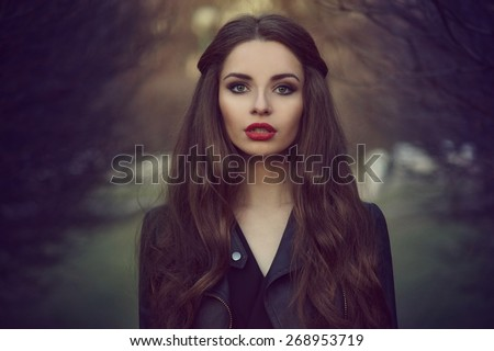 Art portrait of beautiful lonely girl. Pretty woman with long dark hair and red lips posing in forest and looking at you. Shallow DOF - stock photo