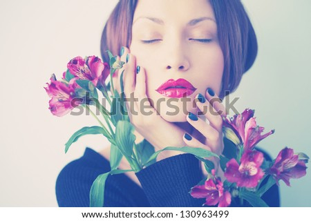 Art portrait of beautiful young lady with delicate flowers - stock photo