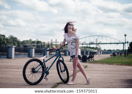 Art portrait of young redhead girl with bicycle on street - stock photo