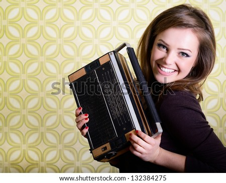 art portrait of young smiling ecstatic woman holding radio player in room with vintage wallpaper, retro stylization 60-70s, toned - stock photo