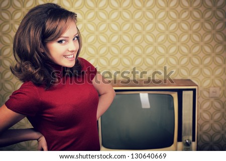 art portrait of young smiling ecstatic woman looking out at camera in room with vintage wallpaper, retro stylization 60-70s, toned - stock photo