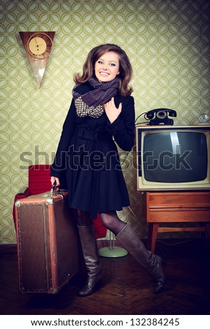 art portrait of young woman holding big suitcase in room with vintage wallpaper and interior with tv, clocks, chair and suitcase, retro stylization 60-70s, toned - stock photo