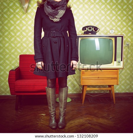 art portrait of young woman standing in room with vintage wallpaper and interior with tv, phone and chair, retro stylization 60-70s, toned - stock photo