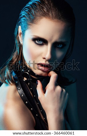Art portrait of young woman with dark make up and leather belt on her neck. - stock photo