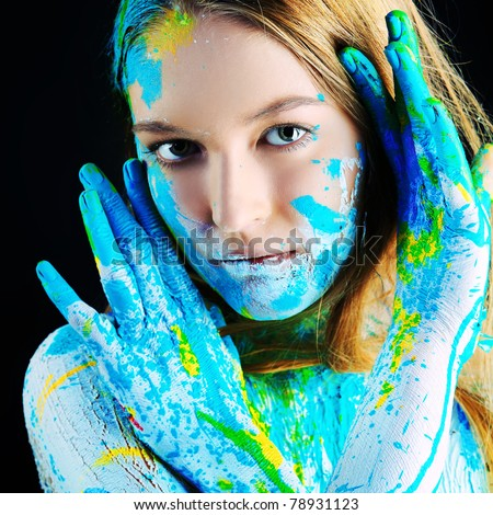 Art project: beautiful woman painted with many vivid colors. Over black background. - stock photo
