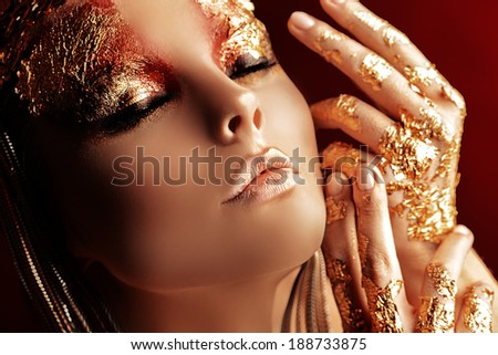 Art project: beautiful woman with golden make-up. Jewelry, make-up. Fashion. Over red background. - stock photo