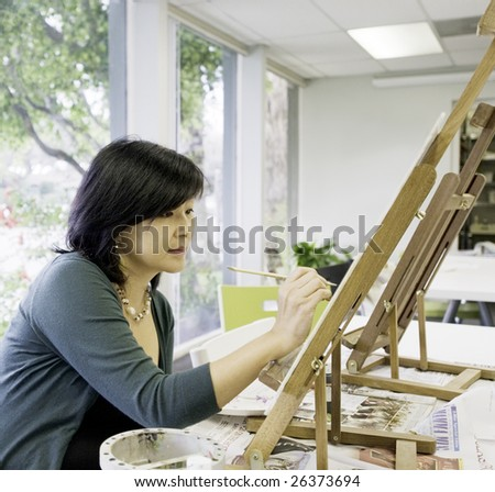 Art teacher paints in preparation for class - stock photo