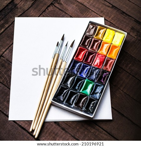 Art tools - Colorful Aquarelle paints in a box. Watercolor Paints and brushes with blank white paper sheet on vintage wooden background close up. - stock photo