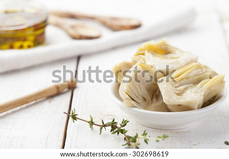 Artichoke hearts marinated in olive oil in a small white bowl on a white wooden background - stock photo