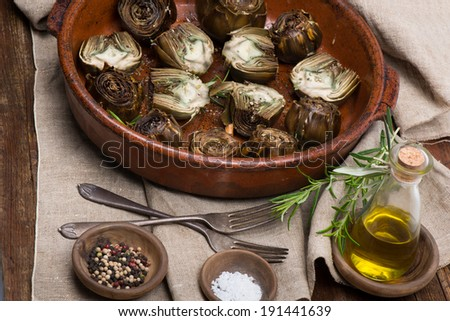 Artichoke hearts on big dish served with olive oil, pepper and salt on the wooden table.  - stock photo
