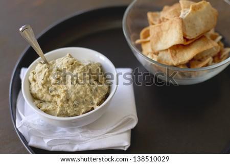 Artichoke hummus with pita chips on a plate. - stock photo