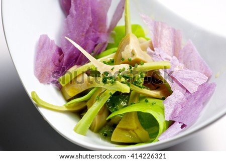 Artichoke salad and blue potato with vegetables. - stock photo