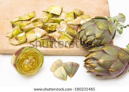 Artichokes cut on cutting board and white background - stock photo