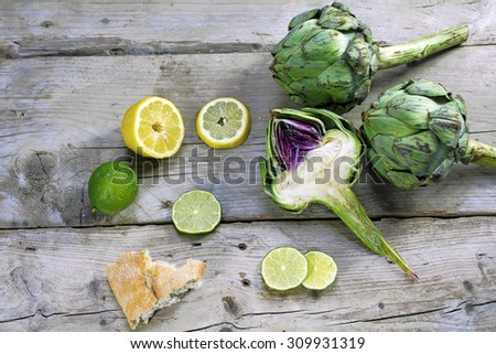 artichokes whole and half, showing the heart, with lemons, limes and bread on an old weathered wooden table - stock photo