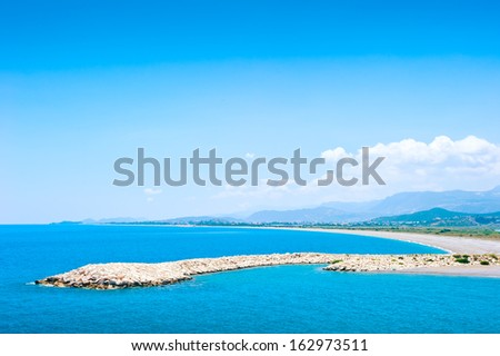 Artificial breakwater in shallow warm waters of the Mediterranean Sea. Demre, Antalya, Turkey - stock photo