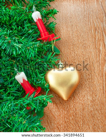 Artificial Christmas tree, electric candles and golden heart on the background texture of oak - stock photo