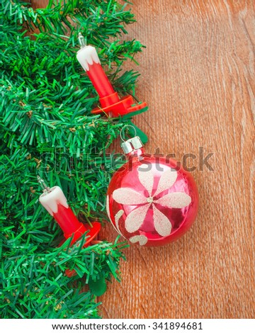 Artificial Christmas tree, electric candles and pink ball on a background texture of oak - stock photo
