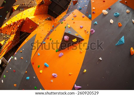 Artificial climbing wall in an indoor climbing gym - stock photo