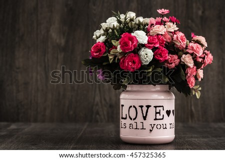 Artificial colorful flowers in a pink flower vase