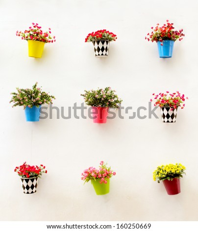 Artificial colorful flowers pots hang onto the wall - stock photo
