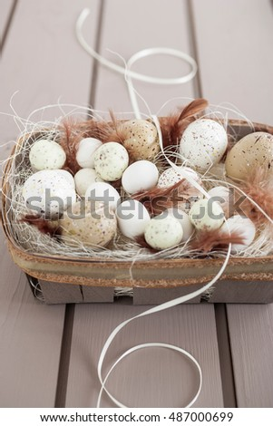 Artificial eggs with feathers decoration in a wooden basket