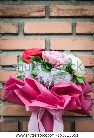 artificial flower bouquet is on a brick wall background