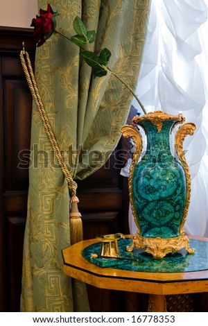 Artificial flower in an antiquarian vase at a window - stock photo