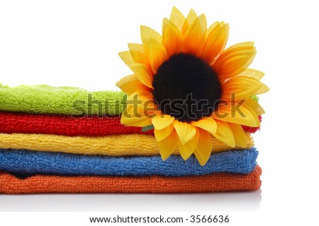 Artificial flower on multicolor towels stacked reflected on white background - stock photo