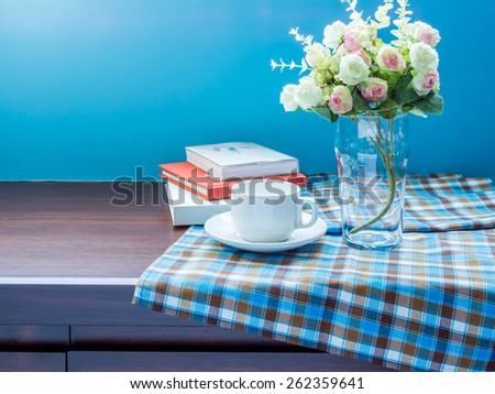 Artificial flower vase with tablecloth on wooden cupboard/ interior still-life concept - stock photo