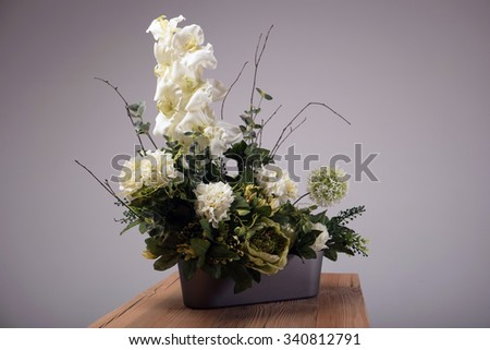 Artificial flowers bouquet in vase on the table - stock photo